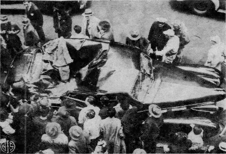 Curious onlookers surround the damaged car, click for larger image